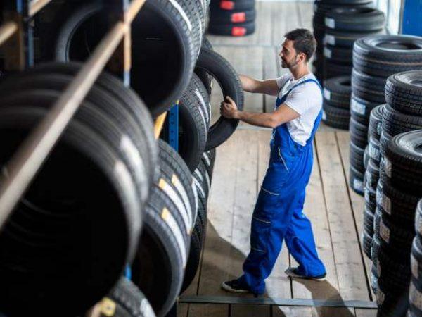 Canva - Auto mechanic choose tire for car.jpg