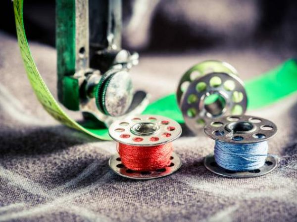 Canva - Closeup of sewing machine and colorful threads on clothes.jpg