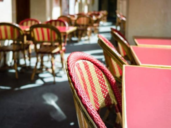 Canva - Typical tables and rattan chairs on the terrace of a parisian outdoor cafe in the sunlight (1).jpg